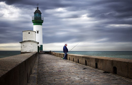 The fisherman / The lighthouse of le Tréport in Normandy (France)